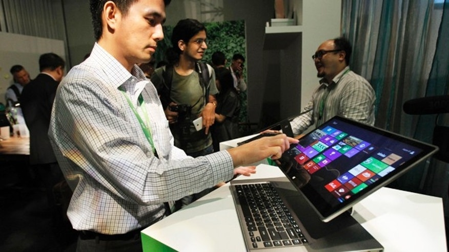 June 3, 2013: An Acer employee displays a new tablet-laptop hybrid Aspire R7 at an international press conference on the eve of the opening of Computex, one of the world&#39&#x3b;s largest IT exhibitions, in Taipei, Taiwan. Aspire R7 features a hinge-attached pad that holds up the touchscreen and allows users to pull the screen closer or flip it over the keyboard, transforming it into a tablet.