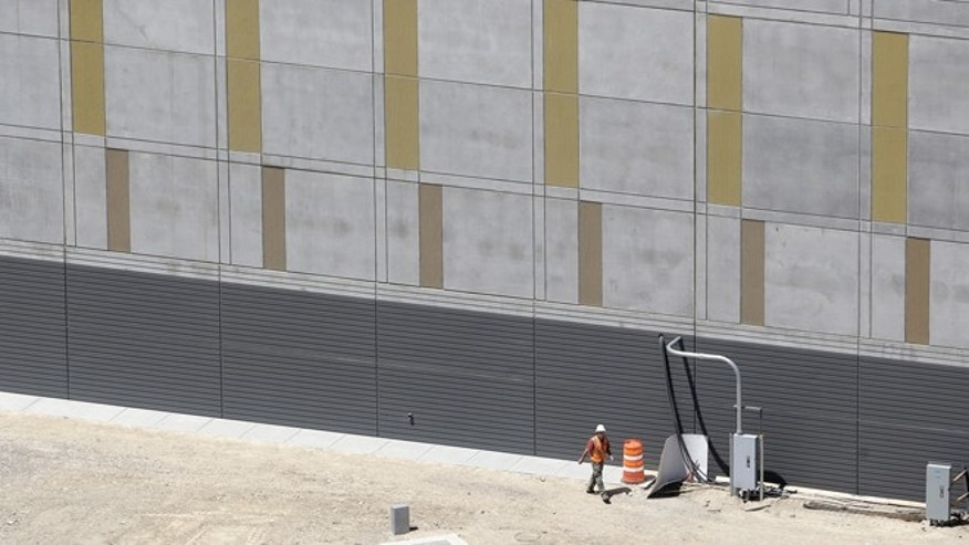 June 6, 2013: This aerial view of the NSA's Utah Data Center shows a worker walking along the front of the complex in Bluffdale, Utah. The government is secretly collecting the telephone records of millions of U.S. customers of Verizon under a top-secret court order, according to the chairwoman of the Senate Intelligence Committee.