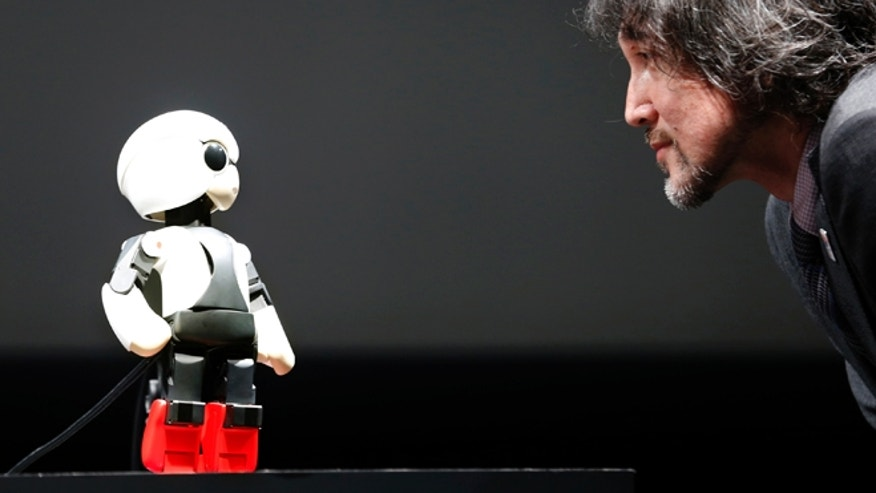 June 26, 2013: Humanoid communication robot Kirobo, left, talks with Fuminori Kataoka, project general manager from Toyota Motor Corp., during a press unveiling in Tokyo.