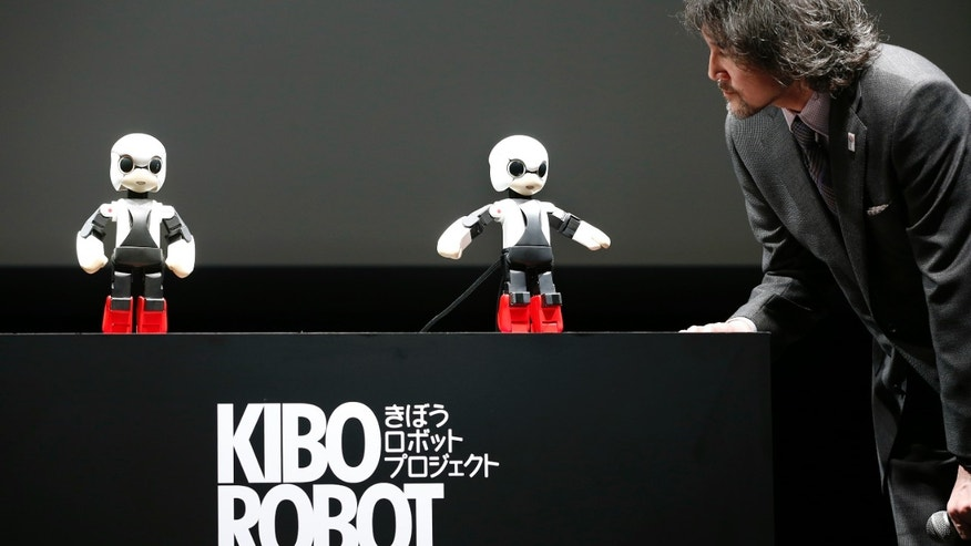 June 26, 2013: Humanoid communication robot Kirobo, center, talks with Fuminori Kataoka, project general manager from Toyota Motor Corp., during a press unveiling in Tokyo.