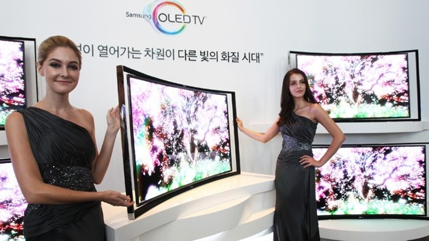 June 27, 2013: Models pose with a Samsung 55-inch curved OLED TV during a press conference at its headquarters in Seoul, South Korea.