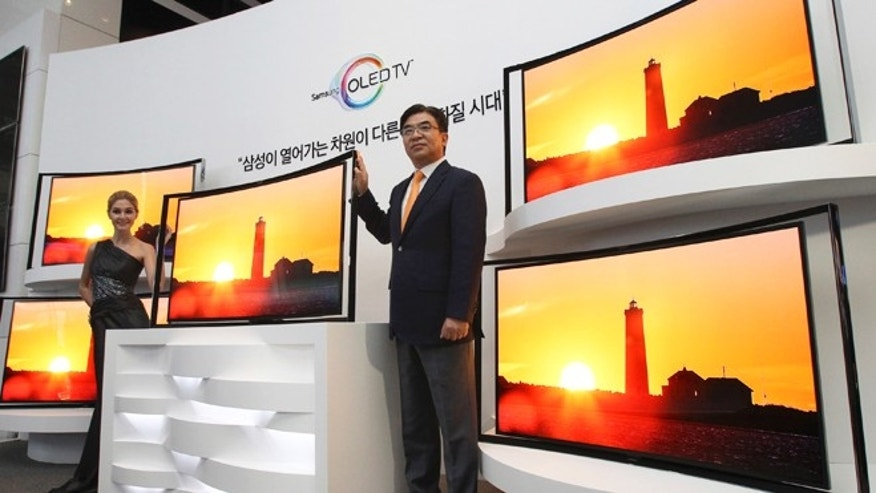 June 27, 2013: Kim Hyunsuk, the executive vice president of Samsung's TV division, right, poses with its 55-inch curved OLED TV during a press conference at its headquarters in Seoul, South Korea.