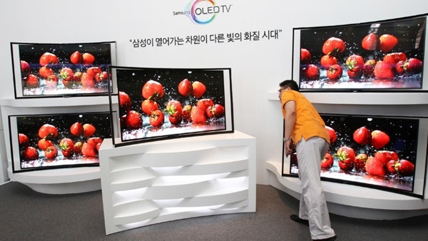 June 27, 2013: A journalist takes a close look at a Samsung 55-inch curved OLED TV during a press conference at its headquarters in Seoul, South Korea.