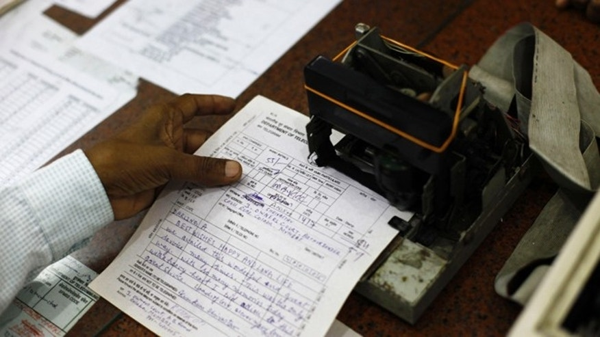 July 14, 2013: An Indian telegraph employee processes a telegram on the last day of the 163-year-old service at the central telegraph office in Mumbai, India.