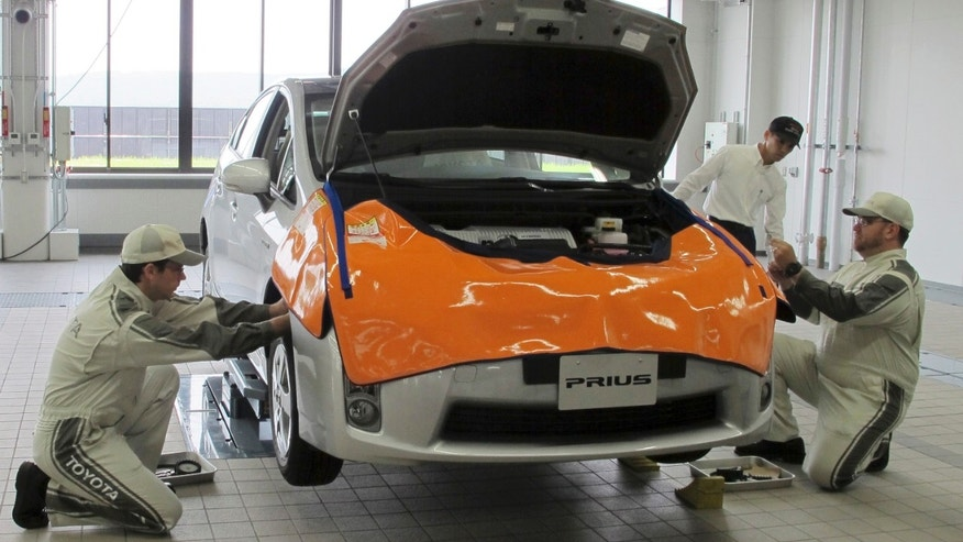 Mechanics work on Prius at a newly completed Toyota's service center in Tajimi, central Japan, Monday, July 22, 2013. Toyota is opening a training facility for mechanics complete with a test course that simulates 13 driving conditions including cobblestones and bumpy roads as part of the automaker's efforts to avoid a repeat of its recall fiasco. (AP Photo/Yuri Kageyama)