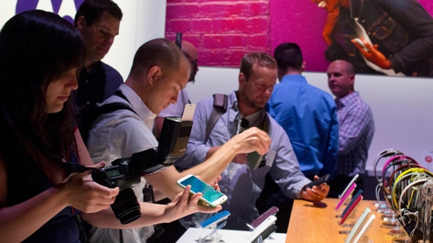 Aug. 1, 2013: Members of the media look at the Motorola Moto X smartphone at a press preview in New York.