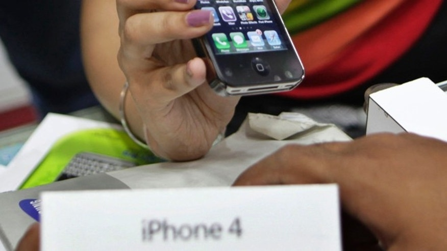 A salesperson at a mobile phone shop displays an Apple iPhone 4.