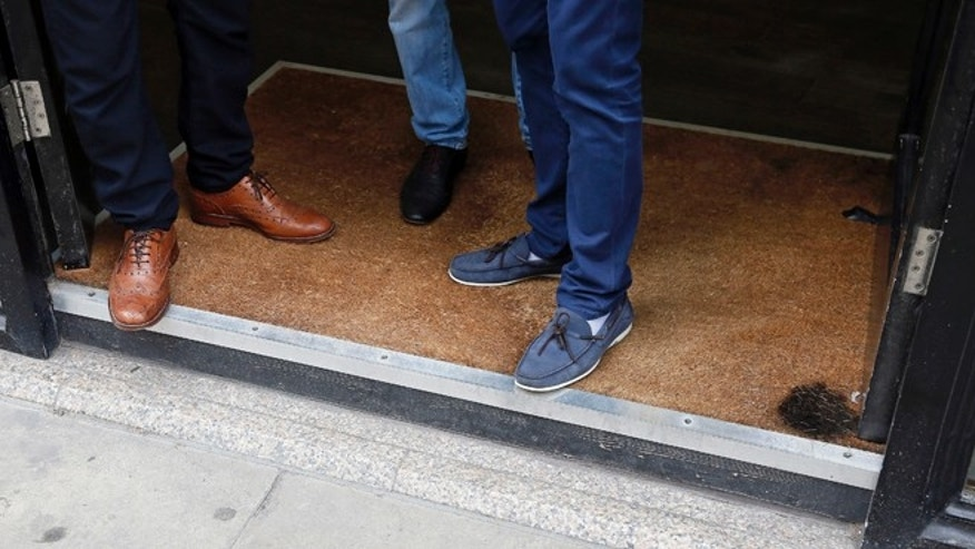 Men stand in the doorway of a barbers shop, which has a burn mark on the carpet in London September 3, 2013. Local media reported the carpet was set alight from sunlight reflected by the Walkie Talkie tower in London.