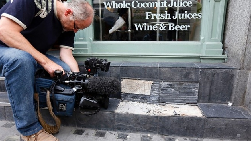 A camera man films broken slates outside a cafe in London September 3, 2013. Local media reported the tiles had shattered from sunlight reflected by the Walkie Talkie tower in London.