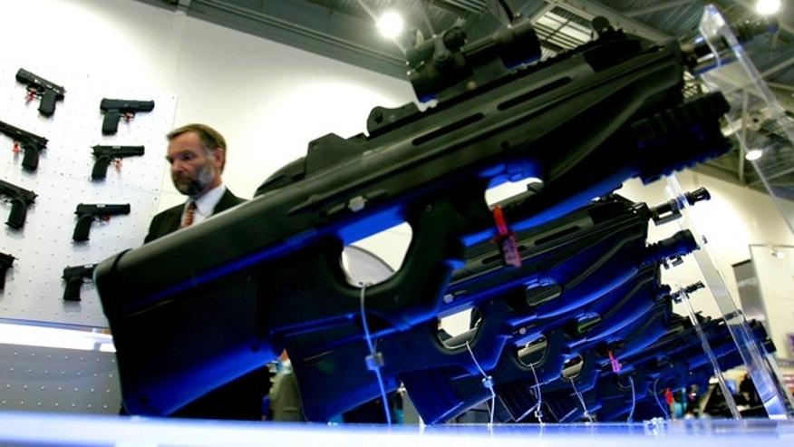 Sept. 9, 2003: A man walks past a tactical F2000 rifle stand at the DSEI (Defense Systems and Equipment International) exhibition, in east London, which is showcasing a range of military hardware from around the globe.