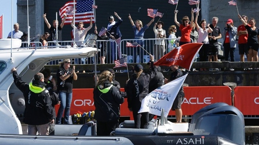 Sept. 24, 2013: Fans cheer as a boat carrying Oracle CEO Larry Ellison passes a pier after Oracle Team USA defeated Emirates Team New Zealand in the 18th race of the America's Cup sailing event in San Francisco.