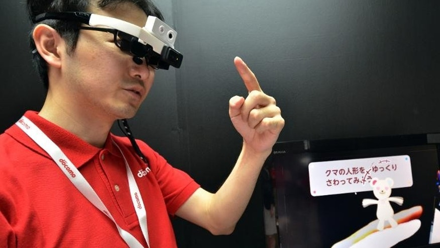 An engineer with Japan's telecom giant NTT Docomo wears a head mount display (HMD) to touch an animation bear for a demonstration at the preview of the Ceatec electronics trade show in Chiba, suburban Tokyo on September 30, 2013