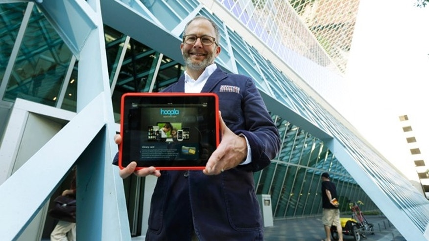Sept. 11, 2013: Kirk Blankenship, Electronic Resources Librarian for Seattle Public Libraries, poses for a photo outside the library as he holds a tablet with the website for streaming-media company Hoopla, which the library is using to offer patrons free access to streaming movies, music, and audiobooks.