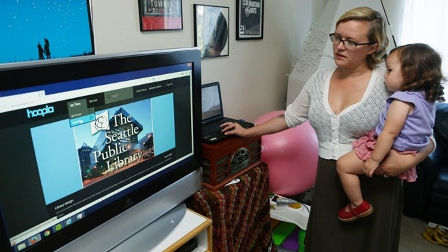 Sept. 11, 2013: Jamie Koepnick-Herrera holds her daughter Paloma, 1 1/2, as they browse for a video to watch on the Seattle Public Library's Hoopla streaming media website.