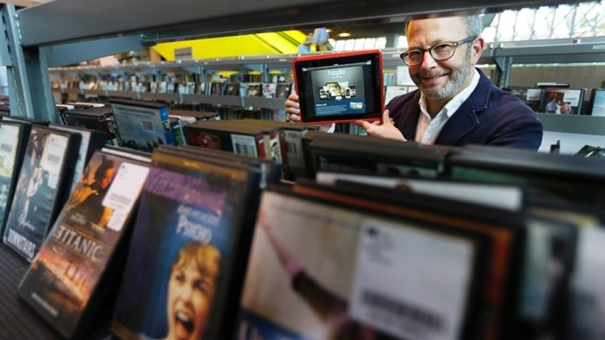 Sept. 11, 2013: Kirk Blankenship, Electronic Resources Librarian for Seattle Public Libraries, poses for a photo in the DVD shelving area of the library as he holds a tablet with the website for streaming-media company Hoopla, which the library is using to offer patrons free access to streaming movies, music, and audiobooks.