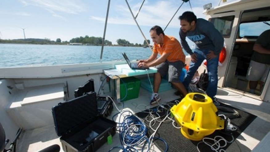 "Doctoral candidates with the University of Buffalo drop two 40-pound sensors into the water to test out an ""underwater Internet"" using sonar rather than radio waves."