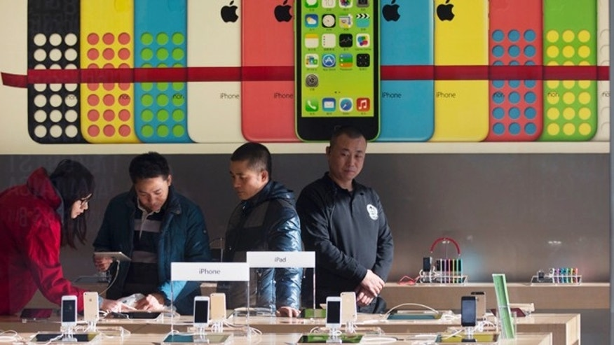 Dec. 23, 2013: Customers look at iPads near an advertisement for the iPhone 5C at Apple's retail outlet in Beijing. Apple and China Mobile announced a long-anticipated agreement Monday to bring the iPhone to the world's biggest phone company.