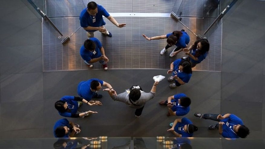 September 20,2013: Chinese employees cheer a customer after he bought a new iPhone at an Apple store in Wangfujing shopping district in Beijing. (AP Photo)