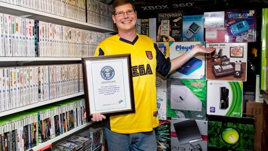 Sept. 1, 2013: Michael Thomasson poses in the basement of his suburban Buffalo home, where he stores his collection of video games. Thomasson is featured in the just-released Guinness World Records 2014 Gamers Edition, for having the largest collection of video games.