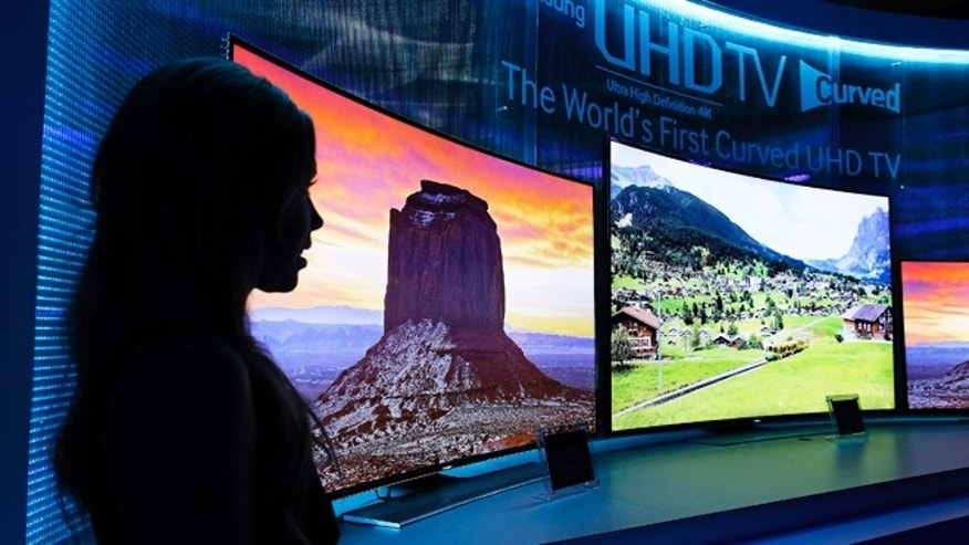 Jan. 5, 2014: A model stands next to a display of Samsung's curved 4K UHD TVs during a preview event at the International Consumer Electronics Show in Las Vegas.