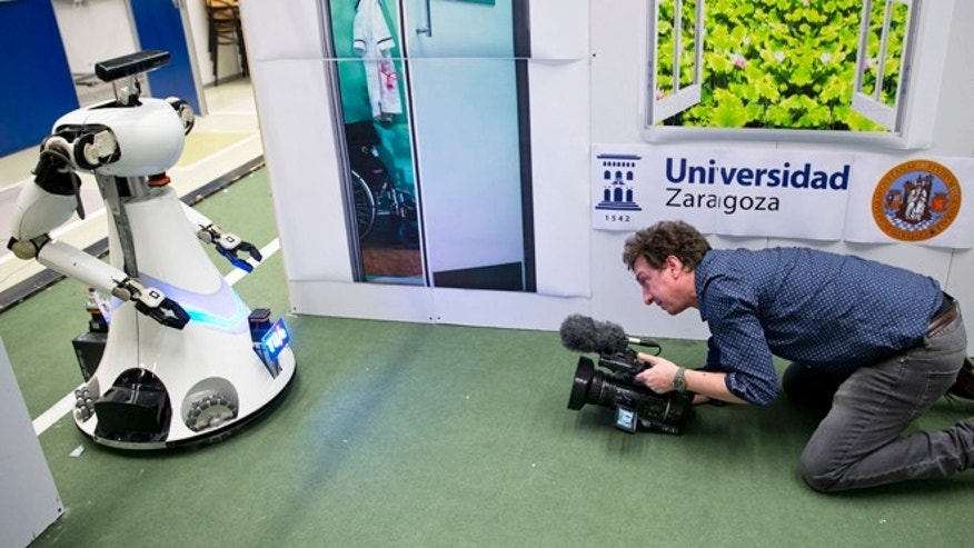 Jan. 15, 2014: A cameraman films Amigo, a white robot the size of a person, who uses information gathered by other robots to move towards a table to pick up a carton of milk and deliver it to an imaginary patient in a mock hospital room at the Technical University of Eindhoven, Netherlands.