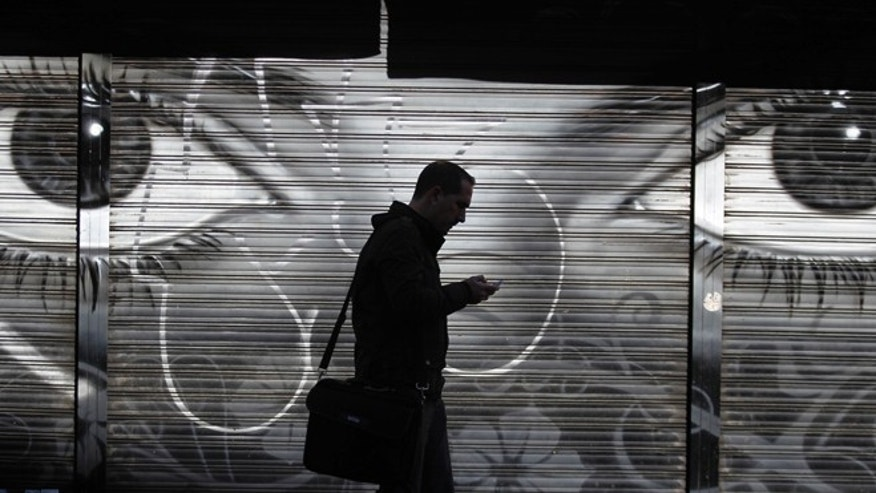 A man looks at his cellphone as he walks on the street in downtown Madrid.