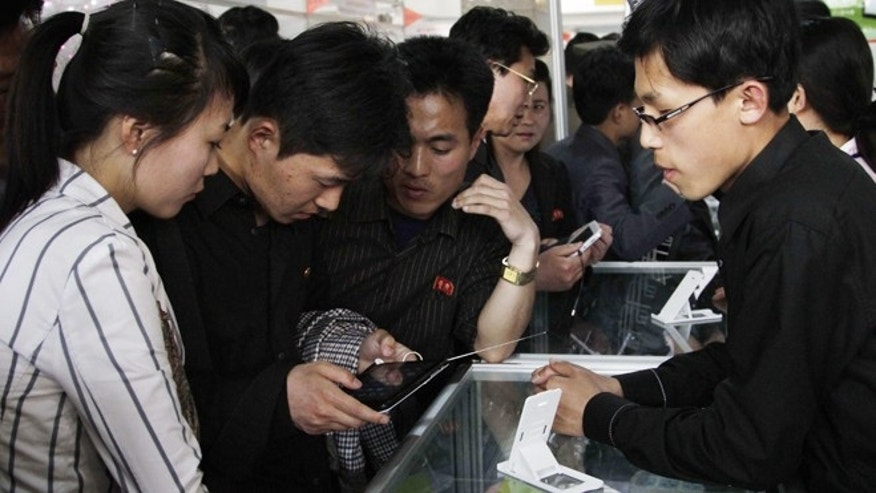 May 15, 2013: Young North Koreans take a closer look at the Samjiyon tablet computer produced for the North Korean market for sale at the 16th Pyongyang Spring International Trade Fair.