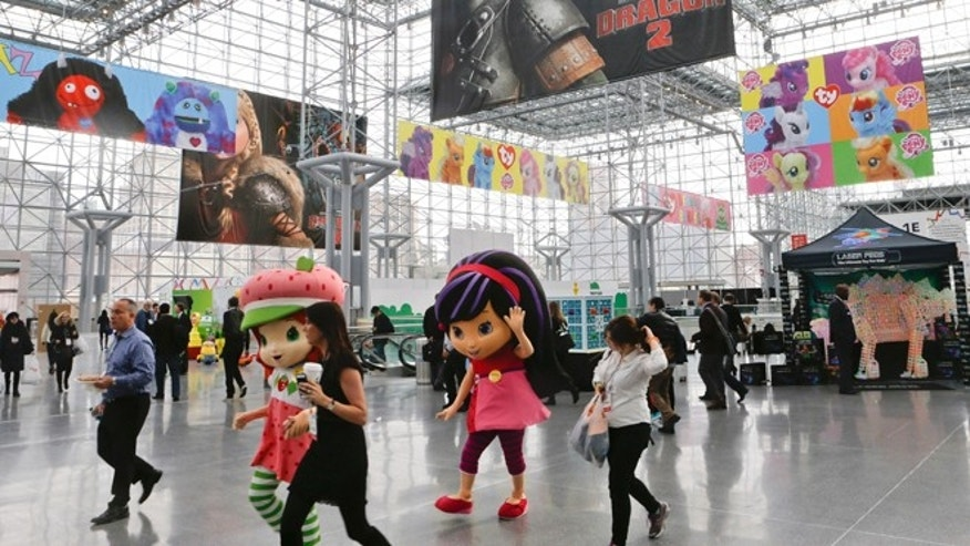 Feb. 16, 2014: Strawberry Shortcake, left, and Cherry Jam, center, walk among people arriving at Toy Fair 2014 at the Jacob K. Javits Convention Center Sunday in New York.