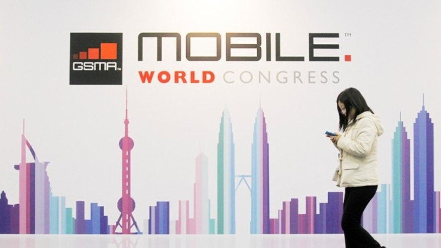 Feb. 28, 2013: A visitor walks past a Mobile World Congress banner in Barcelona.