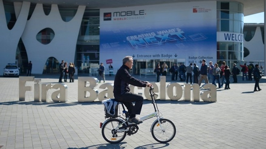A man rides his bicycle outside  the Mobile World Congress, the world's largest mobile phone trade show in Barcelona, Spain, Sunday, Feb. 23, 2014.