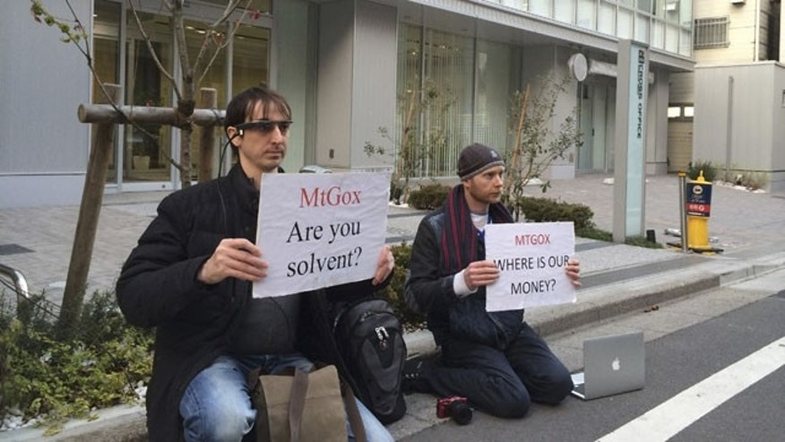 February 25, 2014: Bitcoin trader Kolin Burges, right, of London and American Aaron (only his first name was given) hold protest signs as they conduct a sit-in in front of the office tower housing Mt. Gox in Tokyo. The website of major Bitcoin exchange Mt. Gox is offline Tuesday amid reports it suffered a debilitating theft, a new setback for efforts to gain legitimacy for the virtual currency. (AP Photo)
