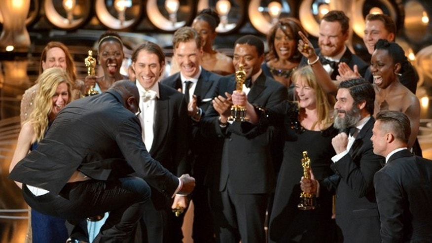 "March 2, 2014: Director Steve McQueen, left, celebrates with the cast and crew of ""12 Years a Slave"" as they accept the award for best picture during the Oscars at the Dolby Theatre in Los Angeles."