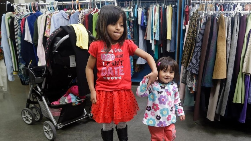 Feb. 21, 2014: Two young girls hold hands as their mother sifts through used clothing at Sacred Heart Community Service in San Jose, Calif.