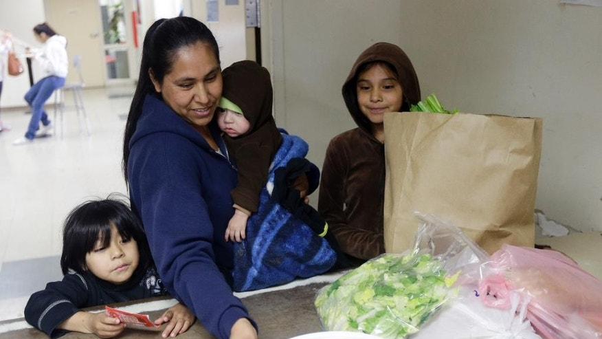 Feb. 21, 2014; A family receives aid at a food pantry at Sacred Heart Community Service in San Jose, Calif.