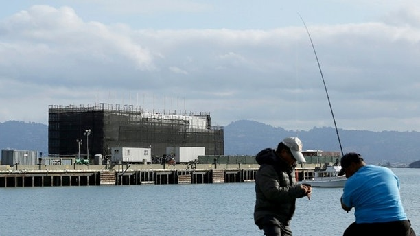Oct. 29, 2013: Two men fish in the water in front of a Google barge on Treasure Island in San Francisco.
