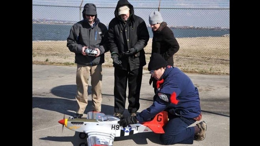 Flying a radio-controlled replica of the historic WWII P-51 Mustang red-tail aircraft—of the legendary Tuskegee Airmen—NRL researchers (left to right) Dr. Jeffrey Baldwin, Dr. Dennis Hardy, Dr. Heather Willauer, and Dr. David Drab, successfully demonstrate a novel liquid hydrocarbon fuel to power the aircraft's unmodified two-stroke internal combustion engine.