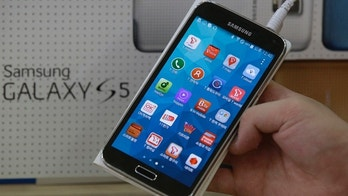 March 27, 2014: An employee shows Samsung's Galaxy S5 smartphone at a mobile phone shop in Seoul, South Korea.