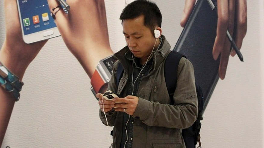 April 8, 2014: A man uses a smartphone near an advertisement for Samsung Electronics Co.'s Galaxy Note 3 in Seoul, South Korea.