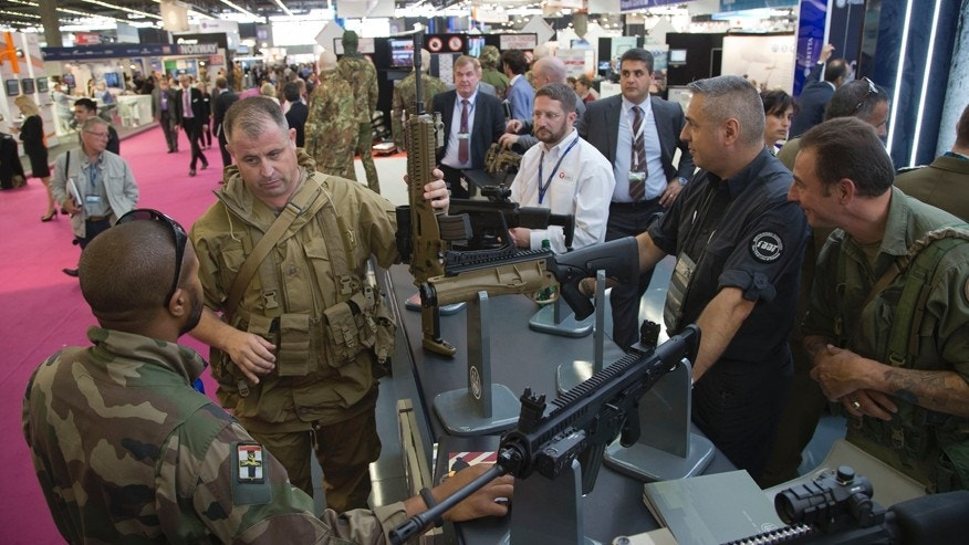A member of the French army, left, looks at a assault rifle manufactured by US company Beretta, presented at the Eurosatory Defence and Security trade show, in Villepinte, outside Paris, Monday, June 16, 2014. Over 1500 exhibitors will take part in the trade show which takes place in the north of Paris from June 16 to June 20.