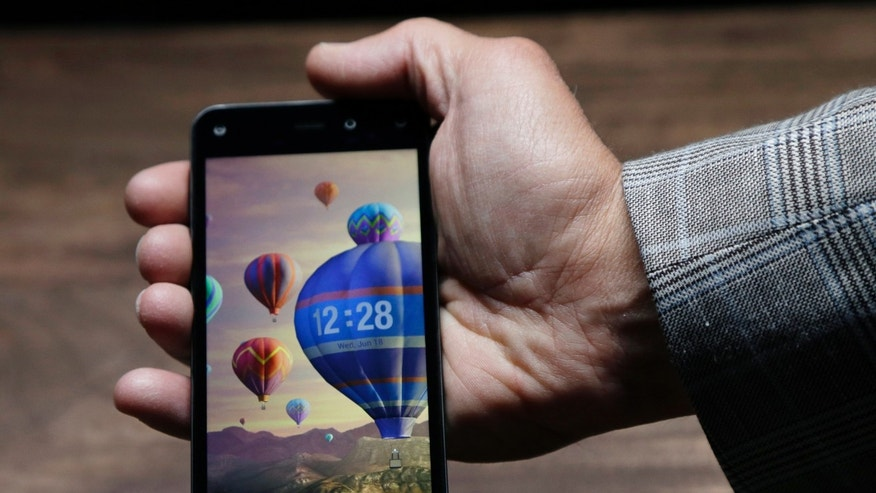 The new Amazon Fire Phone, displaying a dynamic perspective effect lock screen image, is posed for cameras after the official launch event, Wednesday, June 18, 2014, in Seattle. (AP Photo/Ted S. Warren)