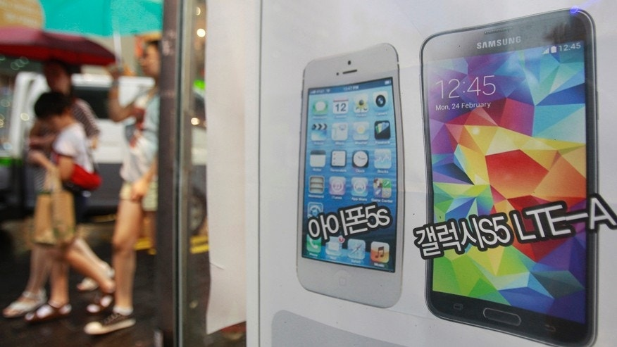 An advertisement poster shows Samsung Electronics' Galaxy S5 LTE-A, right, and Apple's iPhone 5s at a mobile phone shop in Seoul, South Korea, Wednesday, Aug. 6, 2014.