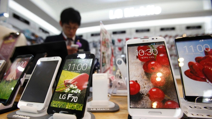 A sales assistant uses his mobile phone in front of mock LG electronics smart phones displayed at a store in Seoul July 22, 2014.