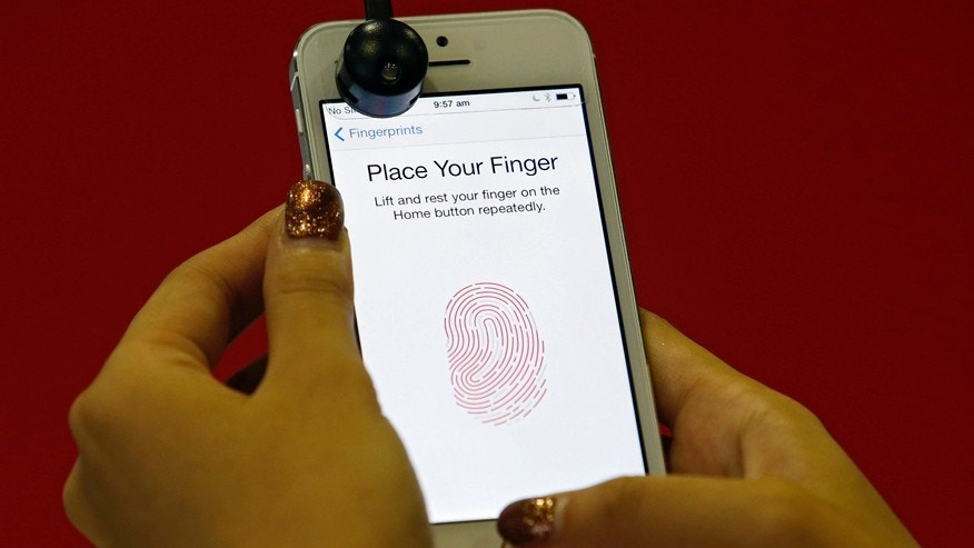 A promoter demonstrates the fingerprint scanner feature of the newly launched Apple iPhone 5S in Singapore September 20, 2013. REUTERS/Edgar Su (SINGAPORE - Tags: SCIENCE TECHNOLOGY BUSINESS TELECOMS) - RTX13RZQ