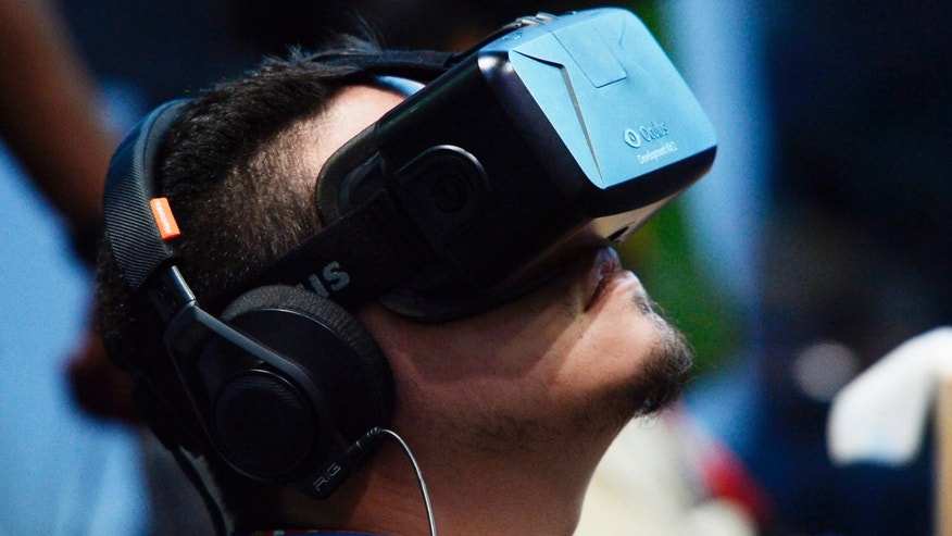 An attendee tries on the Oculus VR Inc. Rift Development Kit 2 headset at the 2014 Electronic Entertainment Expo (E3) in Los Angeles, California June 11, 2014.