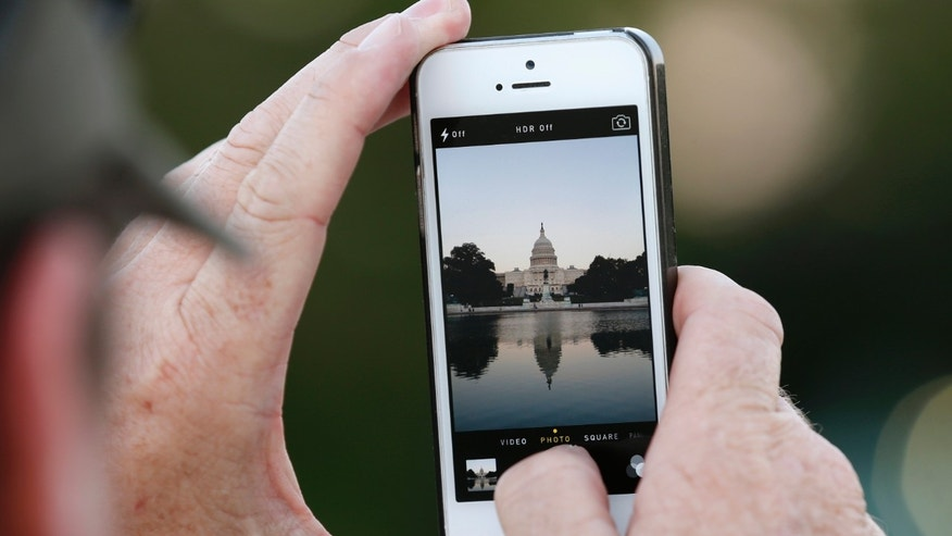 A man takes a photo of the U.S. Capitol, on the eve of a potential federal government shutdown, in Washington September 30, 2013. As many as a million government employees were making urgent plans on Monday for a possible midnight shutdown, with their unions urging Congress to strike a last-minute deal.  REUTERS/Kevin Lamarque (UNITED STATES - Tags: POLITICS BUSINESS) - RTR3FGGG