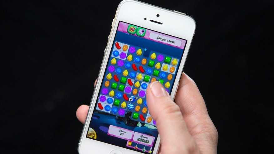A woman poses for a photo illustration with an iPhone as she plays Candy Crush in New York February 18, 2014. King, the Swedish firm behind hit mobile phone game Candy Crush Saga, is planning a U.S. stock market debut which some analysts think could value it at more than $5 billion and herald a flurry of technology company listings this year.   REUTERS/Carlo Allegri (UNITED STATES - Tags: BUSINESS SCIENCE TECHNOLOGY) - RTX19278