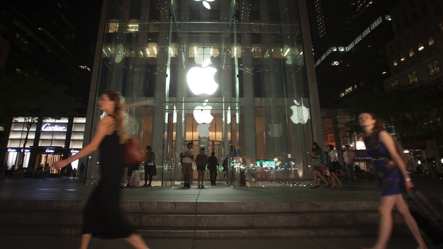 People walk past an Apple store at night in the Manhattan borough of New York September 7, 2014, ahead of the expected release of iPhone 6 and other products this week.