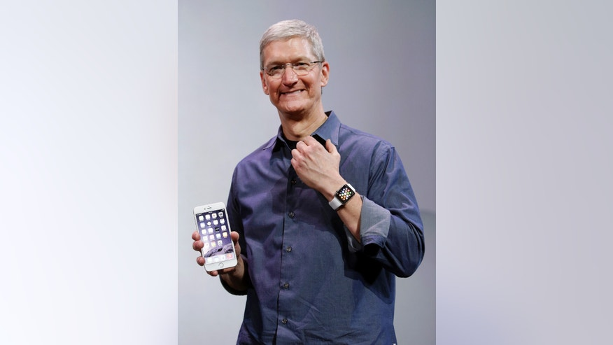 Apple CEO Tim Cook, holding an iPhone 6 Plus, discusses the new Apple Watch and iPhone 6s on Tuesday, Sept. 9, 2014.