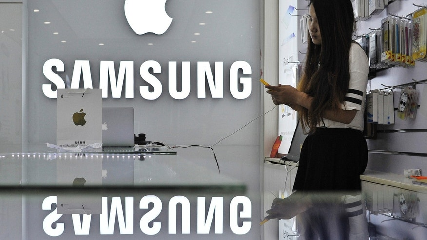 A sales assistant uses her mobile phone next to the company logos of Apple and Samsung at a store in Hefei, Anhui province September 10, 2014.