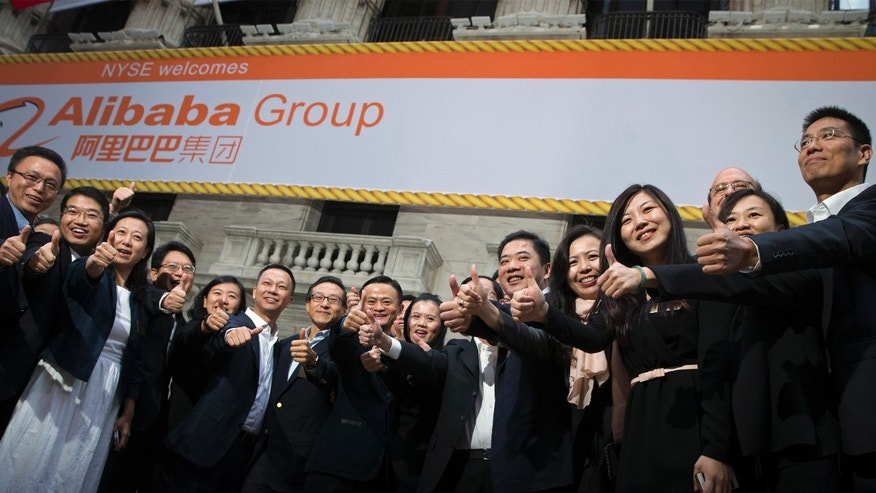 Alibaba Group Holding Ltd founder Jack Ma (C) and Joseph Tsai (center L), vice chairman and co-founder, pose with employees as they arrive for the company's initial public offering (IPO) under the ticker 'BABA,' at the New York Stock Exchange Sept. 19.